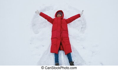 Smiling young woman lies on the snow on a snow angel, waving her hands and sends an air kiss