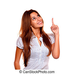 Smiling young woman looking and pointing up