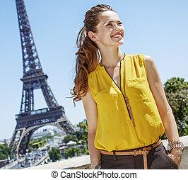 smiling young woman looking aside while in Paris, France -...