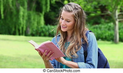 Smiling young woman looking at a book