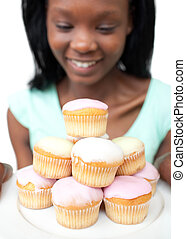 Smiling young woman looking at cakes