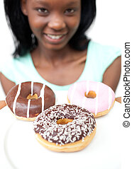 Smiling young woman looking at donuts