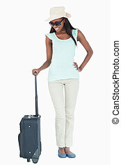 Smiling young woman looking at her suitcase