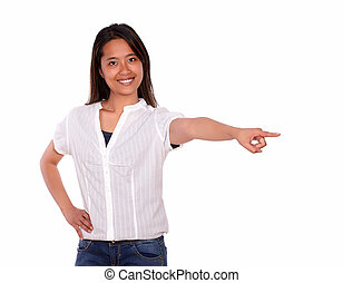 Smiling young woman looking at you pointing left