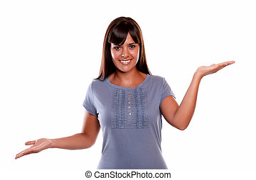 Smiling young woman looking at you with hands up