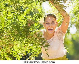 Smiling young woman looking out from foliage