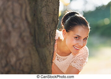 Smiling young woman looking out from tree