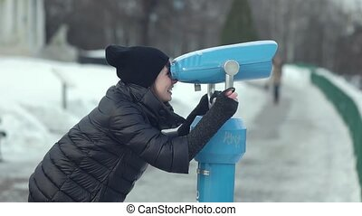 Smiling young woman looking through telescope in winter park...