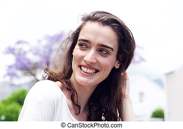 Smiling young woman looking to the side outdoors