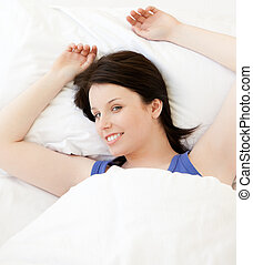 Smiling young woman lying in her bed relaxing