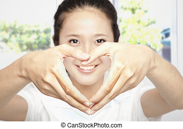 smiling young woman make heart shape