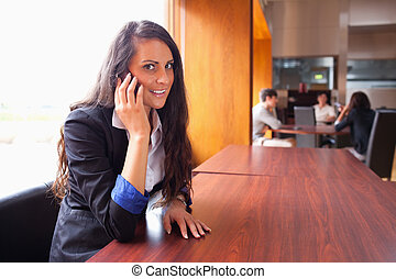 Smiling young woman making a phone call
