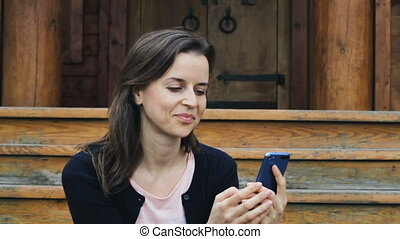 Smiling young woman messaging on mobile and feeling delighted