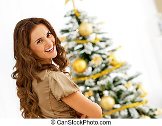 smiling young woman near christmas tree