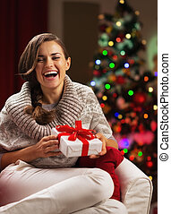 Smiling young woman near christmas tree with present box