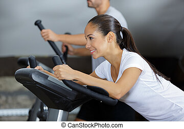smiling young woman on an exercise machine in the gym