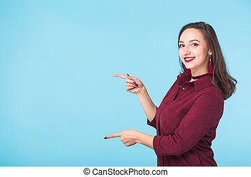 Smiling young woman on blue background with copy space.