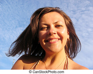 Smiling young woman on blue sky background