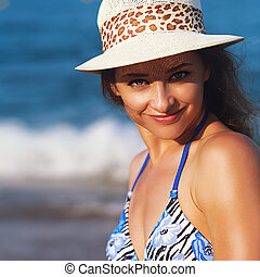 Smiling young woman on bright blue sea background