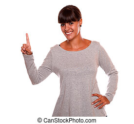 Smiling young woman on grey dress pointing up