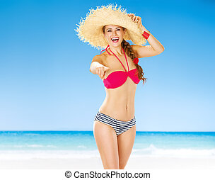 smiling young woman on seashore pointing in camera