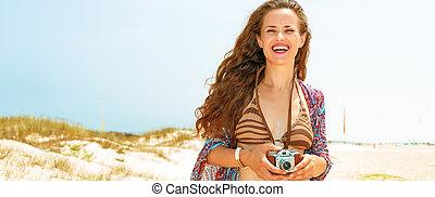 Bohemian vibe vacation. smiling gypsy style young woman in bikini on the seashore with retro photo camera