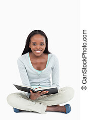 Smiling young woman on the floor with her book