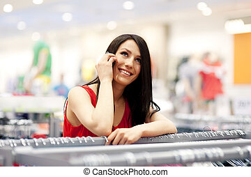 Smiling young woman on the phone at shopping mall
