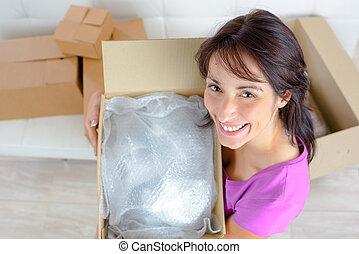 smiling young woman opening a carton box