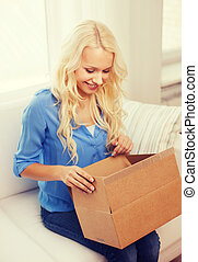 smiling young woman opening cardboard box at home