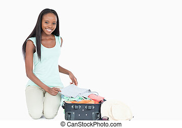 Smiling young woman packing her suitcase