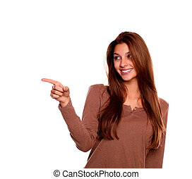 Smiling young woman pointing and looking right