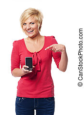 Smiling young woman pointing at screen of mobile phone