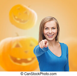 smiling young woman pointing finger at you