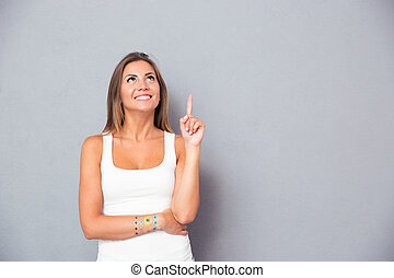 Smiling young woman pointing finger up over gray background