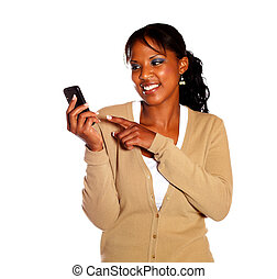 Smiling young woman pointing her cellphone