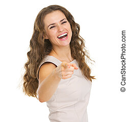 Smiling young woman pointing in camera