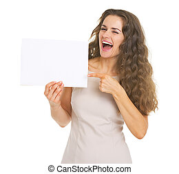 Smiling young woman pointing on blank paper sheet