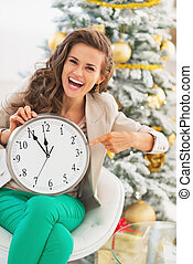 Smiling young woman pointing on clock in front of christmas tree