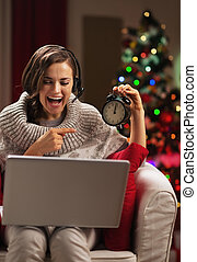 Smiling young woman pointing on clock while having video chat in front of christmas tree