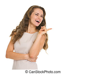 Smiling young woman pointing on copy space