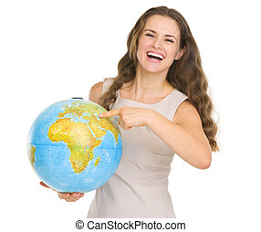Smiling young woman pointing on globe