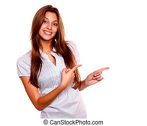 Smiling young woman pointing to her left