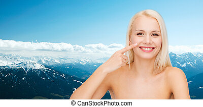 smiling young woman pointing to her nose