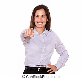 Smiling young woman pointing while standing