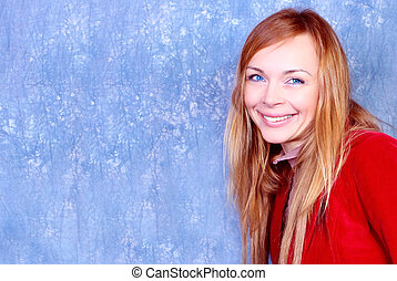 Smiling young woman portrait, in red. Studio shot