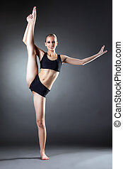 Smiling young woman posing on vertical splits in studio
