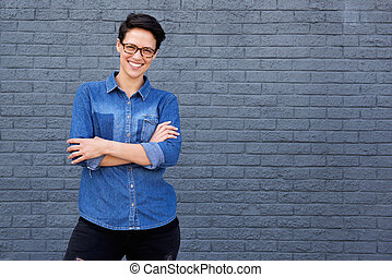 Smiling young woman posing with glasses against gray background