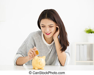 smiling young Woman Putting Coin In Piggy Bank