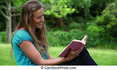 Smiling young woman reading a novel in a park